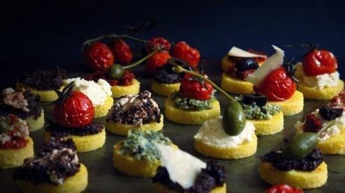 Canapés de polenta, purée de tomates séchées, pesto de câpres, purée d'olives, tomates confites, ricotta et prmesan