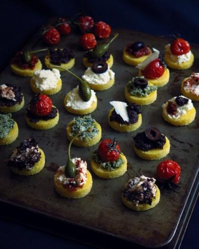 Canapés de polenta, purée d'olives, purée de tomates séchées, pesto de câpres, tomates confites, ricotta et prmesan