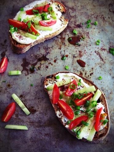 tartines au yaourt grec, vinaigrette de mélasse de grenade et sumac, concombre, tomates et herbes